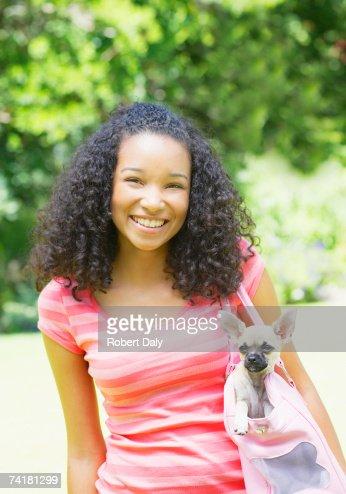Teenage girl with puppy dog in handbag
