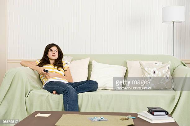 Teenage girl with remote control contemplatively looking away
