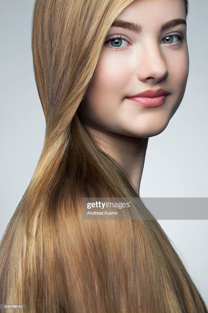 teenage girl with shiny hair over her shoulder stock photo