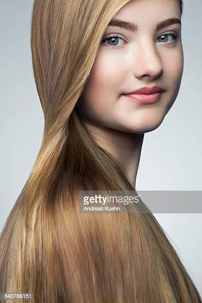 Teenage girl with shiny hair over her shoulder.