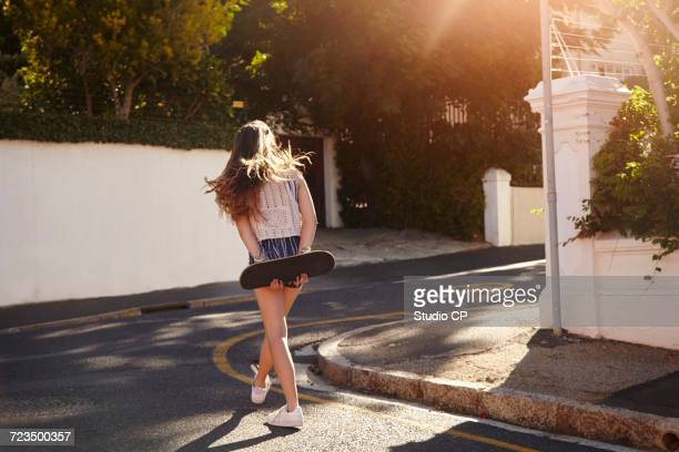 Teenage girl with skateboard in street, Cape Town, South Africa