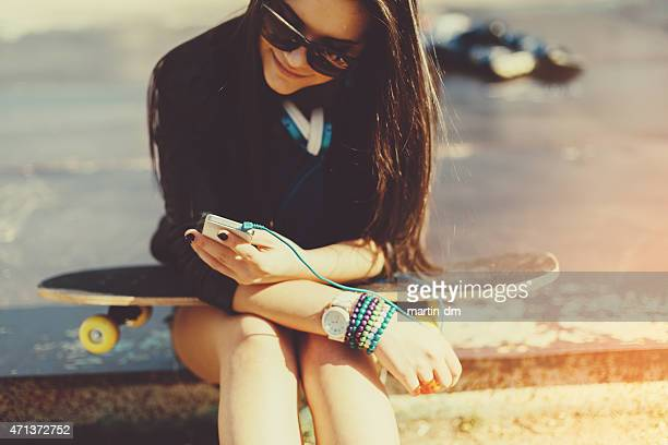 Teenage girl with skateboard texting on smartphone