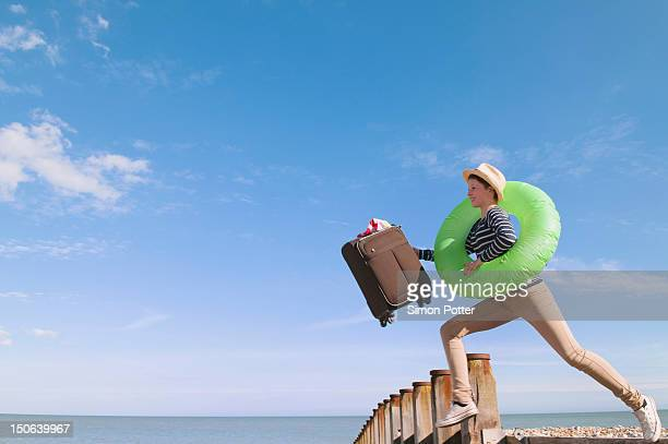 Teenage girl with suitcase on dock