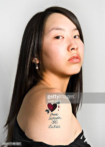 Teenage girl (15-17) with tattoo on upper arm, portrait, close-up