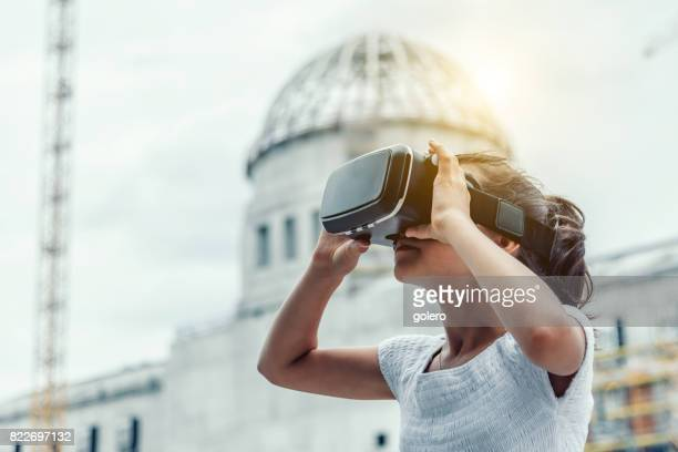 teenage girl with virtual reality simulator outdoors