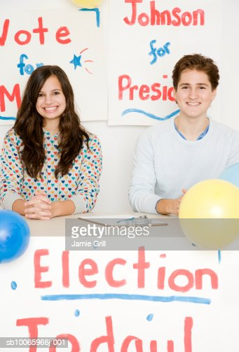 Teenage girl (14-15) with young man at desk running for president election, smiling, portrait : Stock-Foto