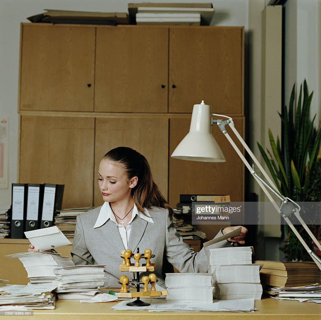 Teenage girl (15-17) working in office,  piles of envelopes on desk