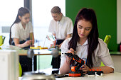 Adolescent girl in a design and technology lesson. She is building a robotic arm and there are other students working in the background.