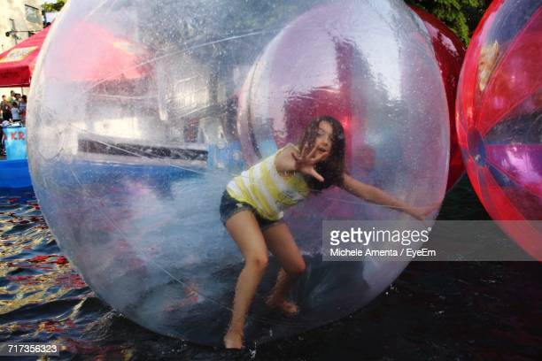 Teenage Girl Zorbing In Swimming Pool