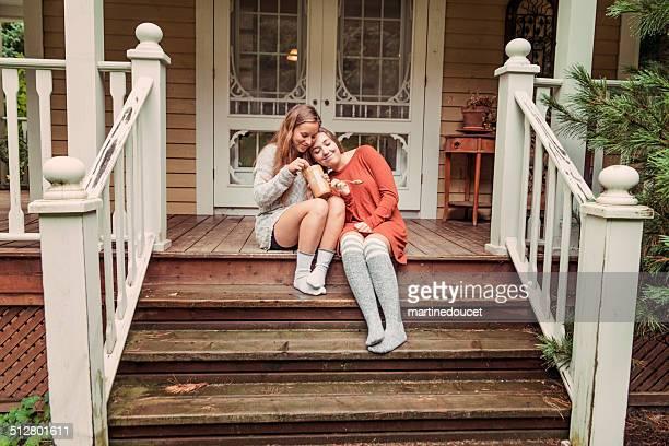 Jeunes copines manger au beurre de cacahuètes, porche de la maison sur un jour de pluie.