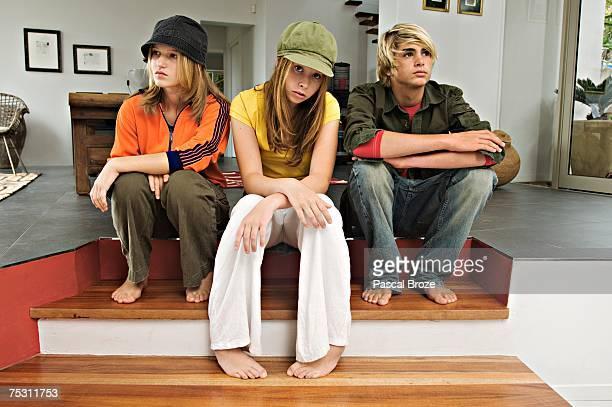 2 teenage girls and 1 teenage boy looking sullen