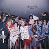 Teenage girls and fans of English pop group The Beatles shout and cheer and hold welcome signs as they wait for the group to arrive at Kennedy...