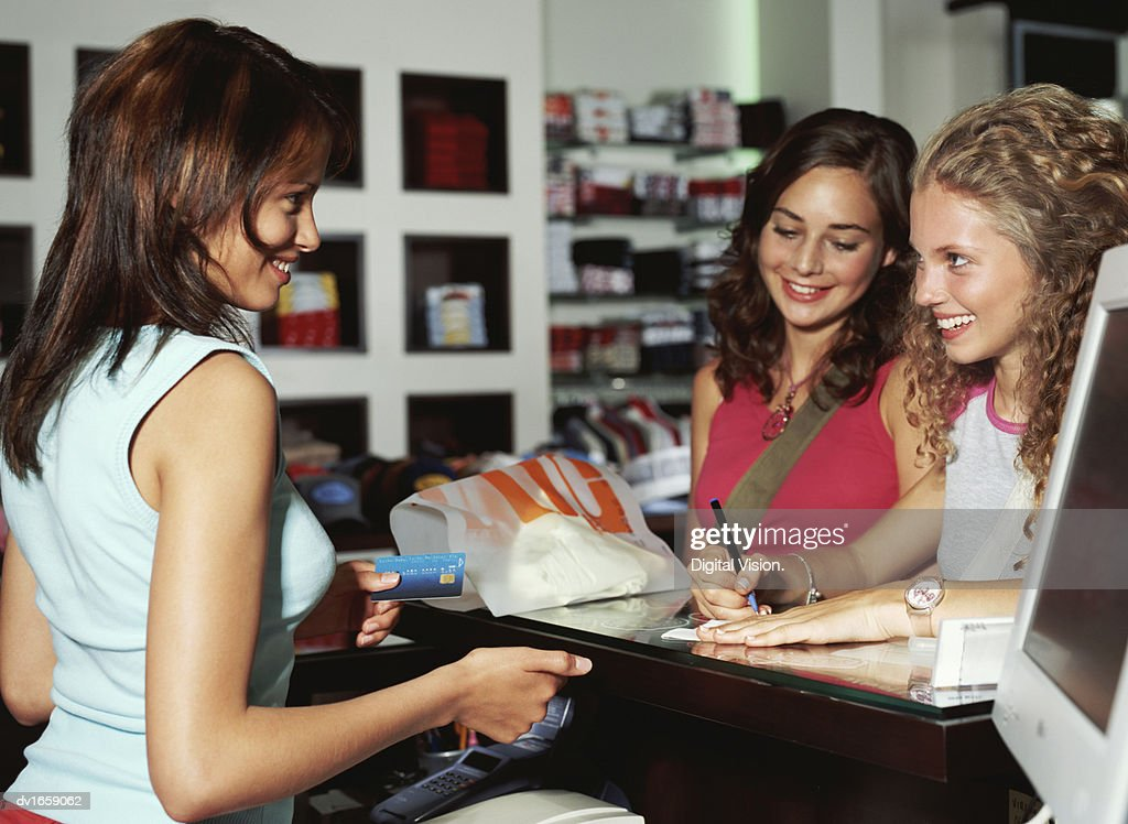 Teenage Girls at a Cash Counter  and a Shop Assistant Holding a Credit Card. Teenage Girls At A Cash Counter And A Shop Assistant Holding A