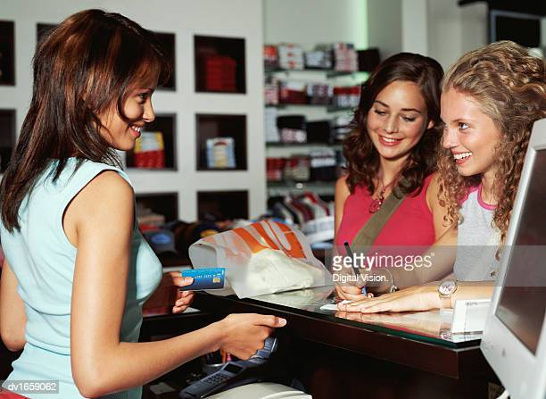 Teenage Girls at a Cash Counter, and a Shop Assistant Holding a Credit Card