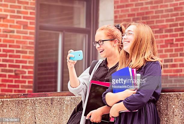 Meninas Adolescentes na escola a tirar uma fotografia com o telemóvel