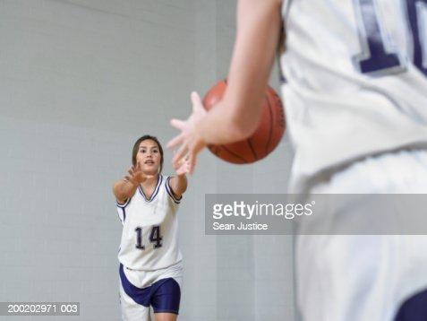 Teenage girls (14-16) basketball players, passing ball : Stock Photo