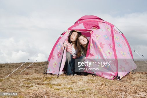 Teenage girls camping in pink tent : Stock Photo