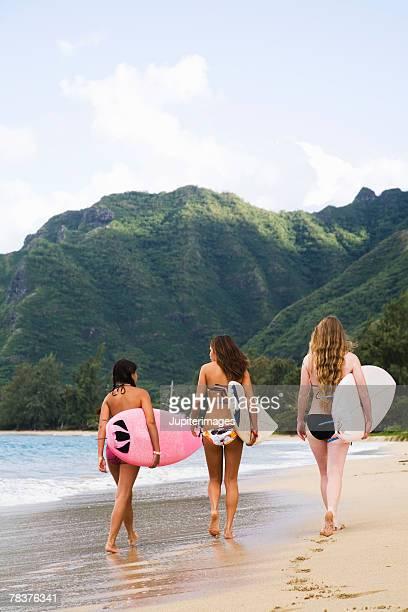 Teenage girls carrying surfboards