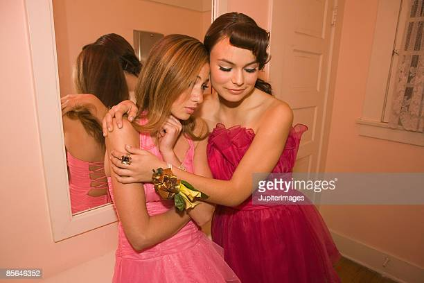 Teenage girls consoling each other in bathroom of prom