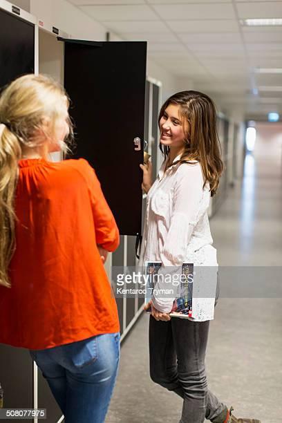 Teenage girls conversing in locker room of high school