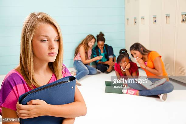 Teenage girls cyber-bully classmate. Gossip, talking. School hall. Lockers.