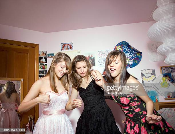 Teenage girls (14-15) dancing in bedroom, smiling
