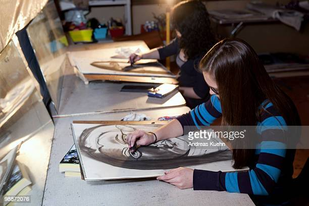 Teenage girls drawing self portraits.