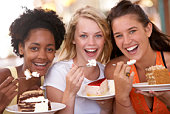 Teenage girls eating cake