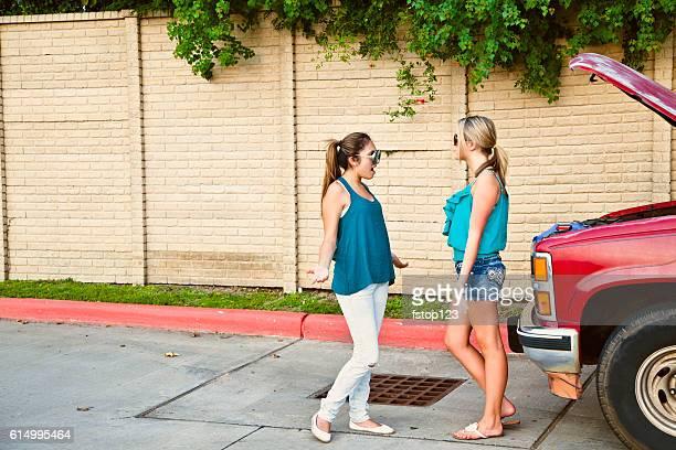 Teenage girls experiencing vehicle breakdown on roadside.