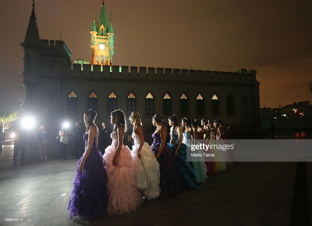 Teenage girls from the Cerro-Cora 'favela', or community, pose before the start of their debutante ball at Ilha Fiscal castle organized by the Pacifying Police Unit (UPP) from their community on November 6, 2014 in Rio de Janeiro, Brazil. The gala was held in the castle on Guanabara Bay and relied on volunteers who prepared makeup, hair dressing and loaned dresses, in an effort to build goodwill between 'favela' residents and the community's police force. Thirteen girls, aged around 15-years-old, attended the ball along with police officers, family members and supporters. The neo-Gothic castle was inaugurated in 1889 and is famed for holding the last Imperial Ball in November of 1889, just six days before Brazil became a Republic.