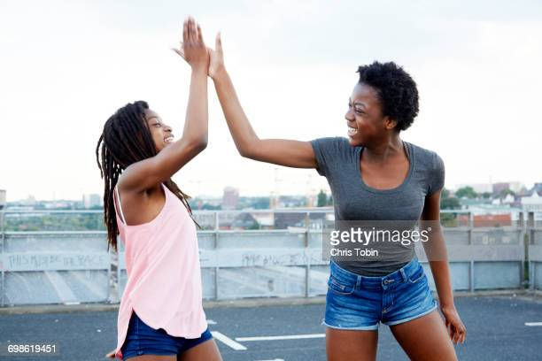 Teenage girls giving each other high five