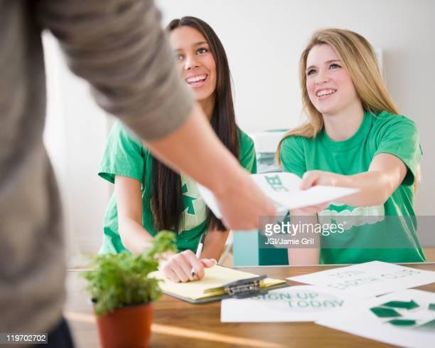 Teenage girls handing recycling brochure to man