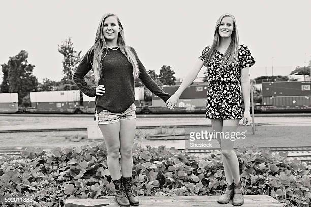 Teenage girls holding hands in train yard