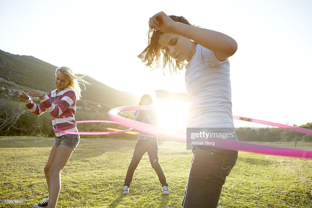 Teenage girls hula-hooping together : Stock Photo