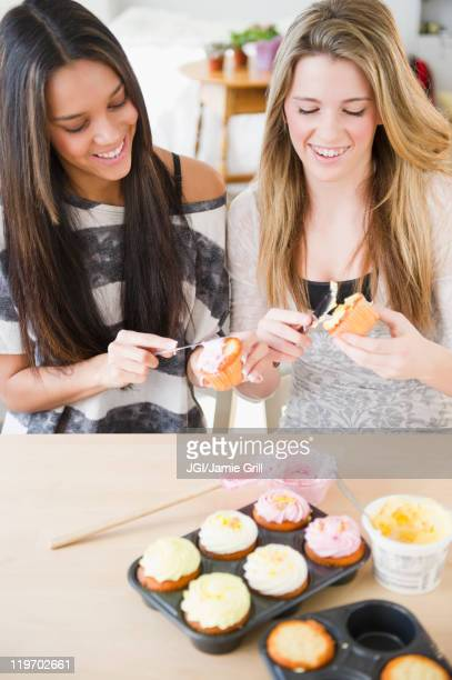 Teenage girls icing cupcakes together