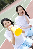 Teenage girls in gym clothes cheering on bench, one holding a megaphone