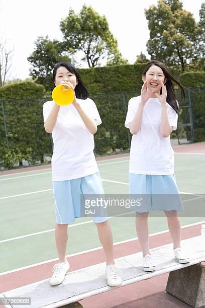 Teenage girls in gym clothes standing on bench and cheering, one holding a megaphone