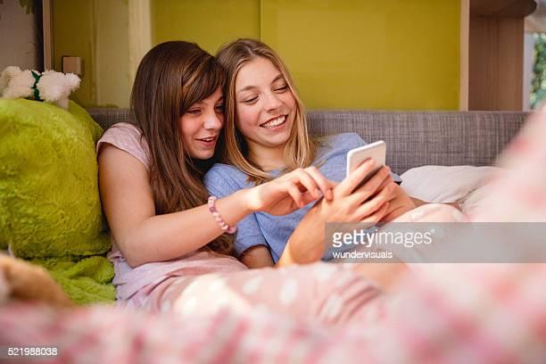 Teenager-Mädchen im Schlafanzug mit Smartphone im Bett Bauchlage
