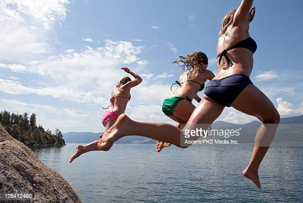 Teenage girls jump of rock cliff into lake below