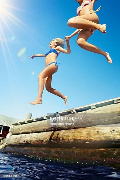 Teenage girls jumping into lake