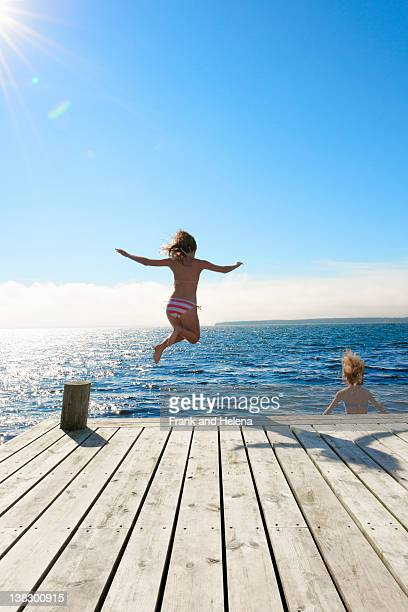 Teenage girls jumping into lake