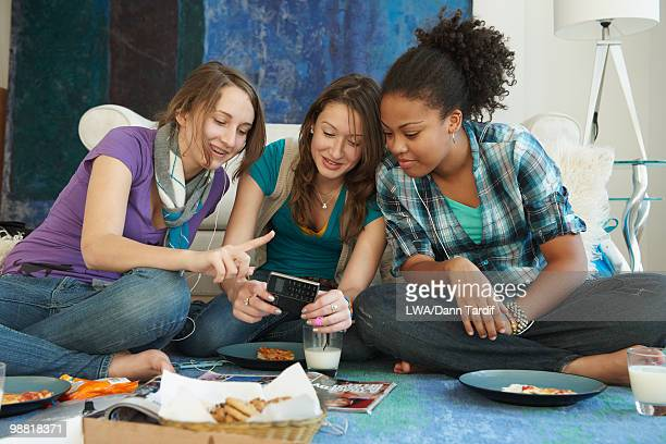 Teenage girls looking at cell phone