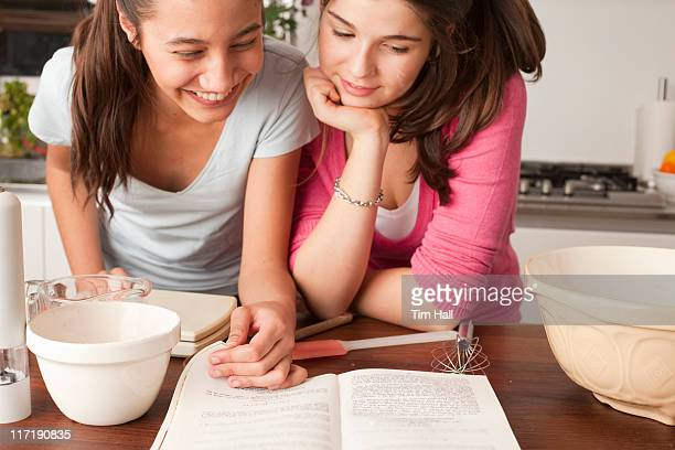 teenage girls looking at recipe in kitchen