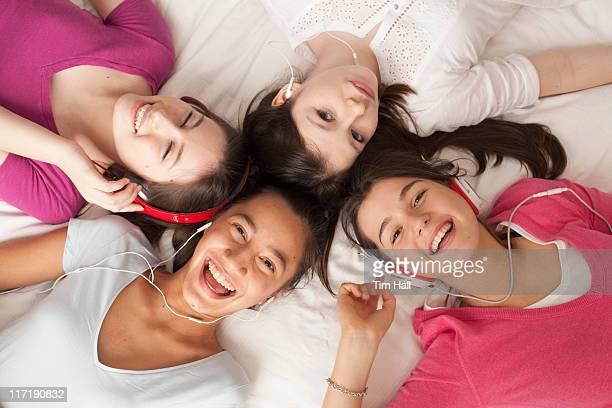 teenage girls lying on floor listening to music, smiling