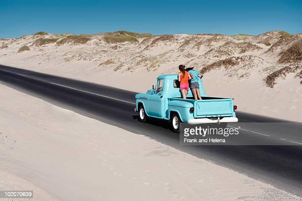 Teenage girls on back of pickup truck