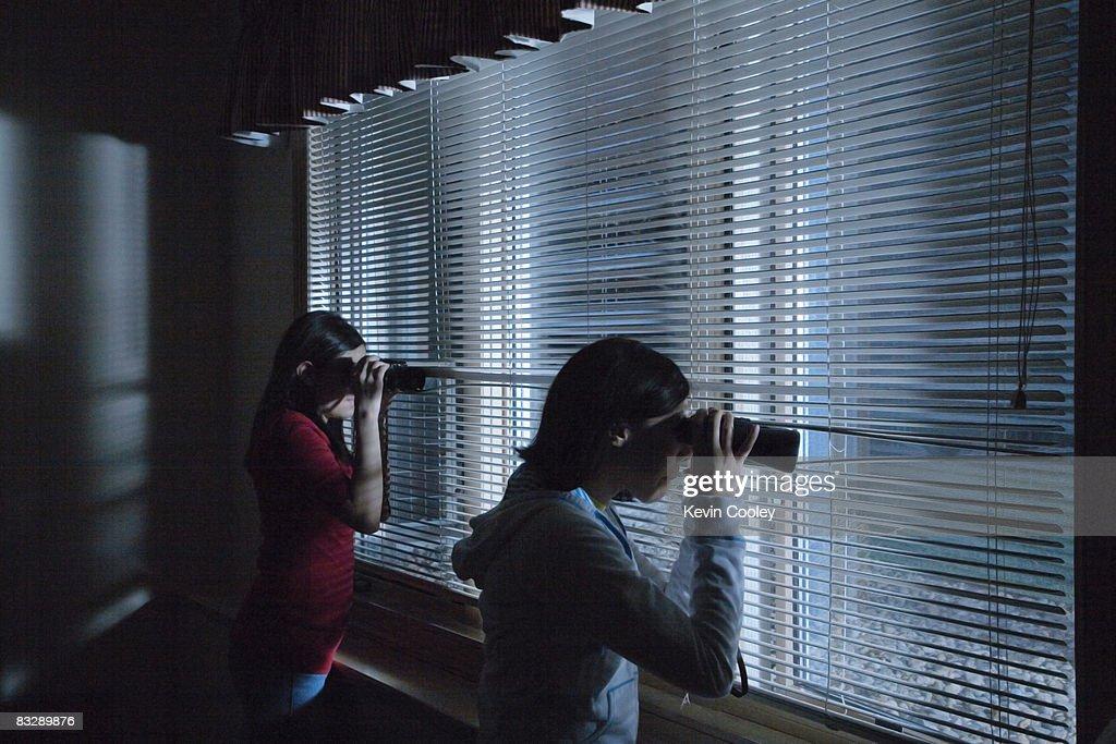 Teenage girls peering out bedroom window  : Stock Photo