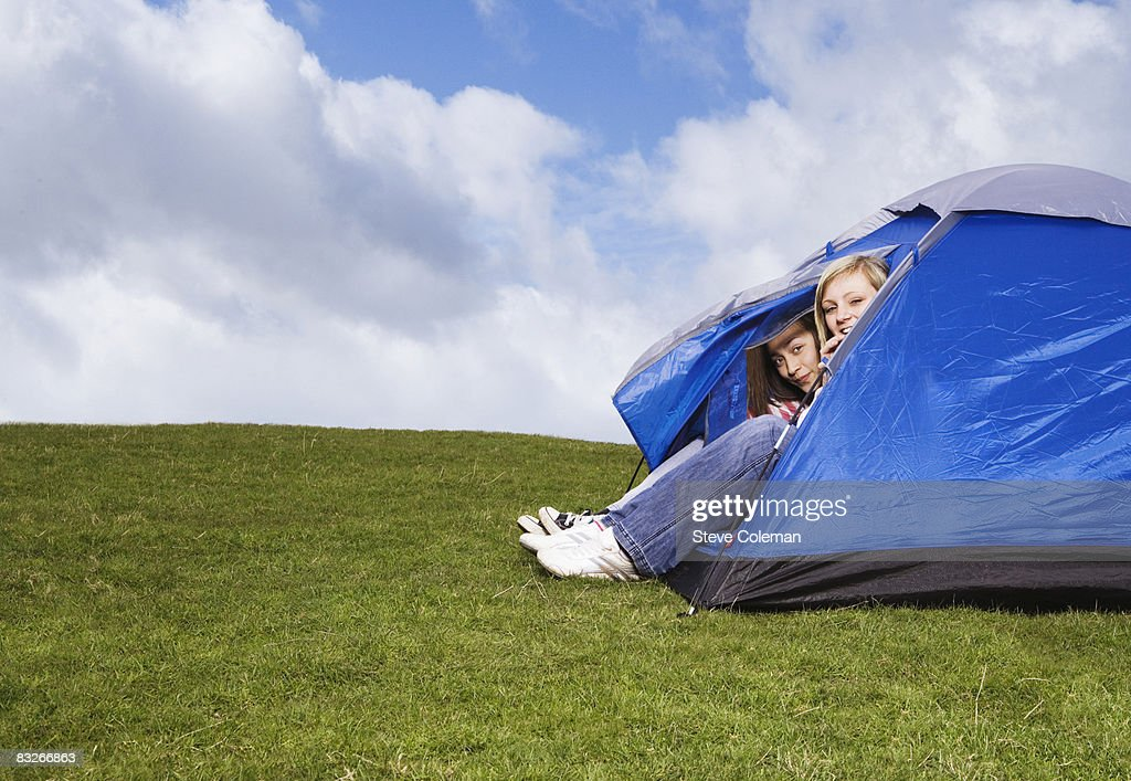 Teenage girls peering out of tent : Stock Photo