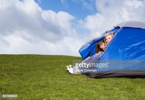 Teenage girls peering out of tent : ストックフォト