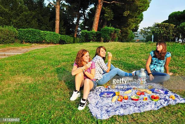 Teenage girls picnicking in rural field