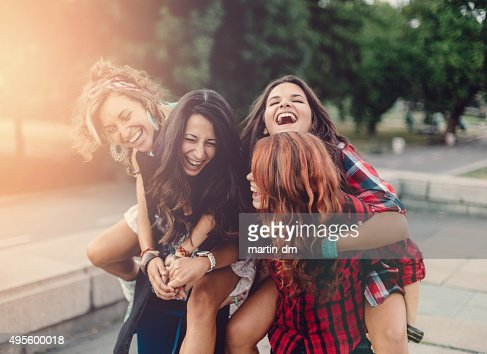 Teenage girls piggyback outside